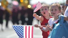 Emily Johnson, left, and Cody Miller wave flags at a parade.