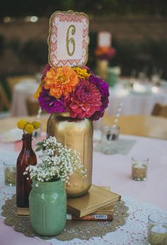 vibrant purple, orange and pink flowers in a painted mason jar centerpiece