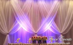 This backdrop is draped in light and flowing ivory sheer fabric.  Accentuated with soft purple uplighting.