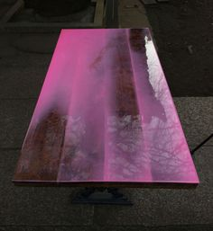 "'flat table' by schemata architecture office    ""flat table' has been created by japanese firm schemata architecture office. using an antique table they   have added a fluro pink epoxy resin to its surface. shallow areas of the table surface are transparent."""