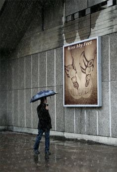 Man standing in the rain looking at a billboard with a foot picture saying 'Kiss My Feet'. Foot worship