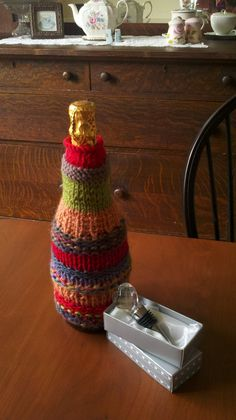 Scrap Yarn Wine Cozy. Knit a tube in the round by CO about 28 to 30 sts. and dividing between 3 needles. I used size 5 needles. Knit about 7 rows in knit 2, purl 2 ribbing. Then change to stockinette until desired length, adding a few purl rows in areas for contrast. Decrease at the beginning of each stitch for a few rows to form neck. Do last 7 rows in knit two purl two ribbing or stockinette.This is free form so have fun! BO