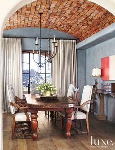 Plaster walls tinted a dusty blue fashion a serene backdrop for the dining room's rustic firebrick ceiling and aged French oak flooring.