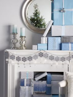 Decorate: Make your mantel the focal part of your home by stacking gifts, lighting candles and hanging garland—all in icy hues.