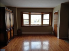 Natural trim around windows, white baseboard & additional trim, natural door and wood floors