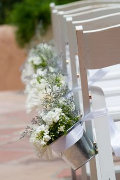 Place flowers that match your wedding colour scheme in vessels that can be tied with ribbon or twine to chairs during the ceremony. And, as a bonus, these can also then be used as centrepieces on tables or as decorative stand-alone elements during the reception.