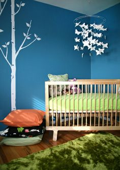This striking and colourful nursery is softened with some organic shapes: the white tree wall sticker and white butterfly mobile.