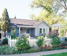 Blooming shrubs and a white picket fence accent this home's cottage style. See more front yard flower gardens: http://www.bhg.com/gardening/landscaping-projects/landscape-basics/front-yard-flower-power/#page=3
