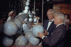 Melville B. Grosvenor, Editor of the Magazine and President of the Society, admires new globes on a conveyor belt in a Chicago plant, December 1961.Photograph by Bates Littlehales, National Geographic