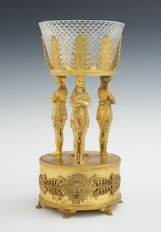 A French Neoclassical Gilt Metal and Diamond Cut Crystal Caryatid Centerpiece  Cast gilt metal basket with fern fronds nesting a diamond cut crystal bowl with radiant design on the bottom, supported by three standing Caryatids in tunics, resting on large circular pedestal with pine cone finial over a flower, pair applied decorations, Classical masks flanked with blooming acanthus leaf design, raised on six paw feet.