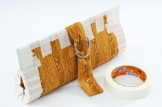 Ainda com a cola úmida, feche a carteira e aplique fita-crepe em suas laterais, para que a bolsa mantenha o formato e possa ser fechada. Esp...