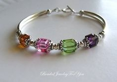 Mother's birthstone bracelet...silver tubes, spacer beads, bead caps, Swarovski crystals.
