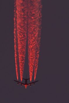 Sunlight reflecting off of a Boeing 747 jets contrails at high altitude.