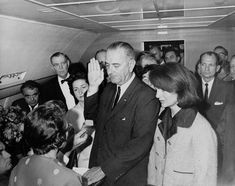 """Jacqueline Kennedy wears her pink Chanel suit, still stained with the blood of her husband, as Lyndon Johnson takes the oath of office in Air Force One.  According to Lady Bird Johnson, who was also present:  """"Her hair [was] falling in her face but [she was] very composed … I looked at her. Mrs. Kennedy's dress was stained with blood. One leg was almost entirely covered with it and her right glove was caked, it was caked with blood – her husband's blood. Somehow that was one of the mo"""