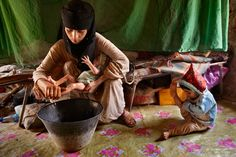 Asia, a 14-year-old mother, washes her new baby girl at home in Hajjah while her 2-year-old daughter plays. Asia is still bleeding and ill from childbirth yet has no education or access to information on how to care for herself.