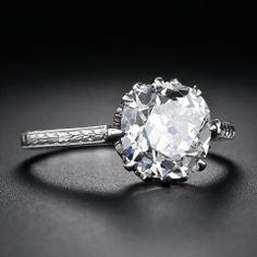2.90 Carat Antique Cushion-Cut Diamond Engagement Ring Circa 1915  This gorgeous Edwardian-era solitaire diamond engagement ring, elegantly presents a 2.90 carat antique cushion-cut diamond.The glorious diamond dazzles solo from an exquisitely detailed platinum engagement ring adorned with afleur de lys motif gallery and delicate hand engraving throughout. Understated elegance par excellence.    Inventory No. 10-1-5175  Price  $27,750