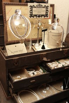 Creative jewelry display. Old jewelry chest, and BIG wide glass bottles.