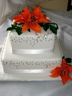 This cake has black and white piped dots on the sides in a random pattern with orange tiger lilies