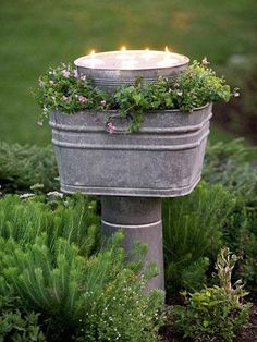 Raised lighting    Floating candles offer illumination for an evening garden party. A raised, galvanized tub overflows with delicate flowers; inside, a smaller tub holds the floating candles.