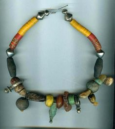 by Anne Marie of BeadArt Austria | Necklace; An ancient Roman bronze ring is the focal piece of this necklace . It is surrounded with genuine amber (Bernstein) Hebron beads in green and yellow, Tuareg crosses from Zinder in Niger, antique spindle whorls made from cow horn and clay, etc. The neckpart is strung with bakelite heishi from the African Trade and Tuareg metal beads. Sterling silver clasp | Sold