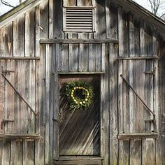 Dress Up Outdoors | Make sure that the style of the wreath matches your outbuilding. Here a simple, rustic wreath complements the charm of a raw wood barn. | SouthernLiving.com