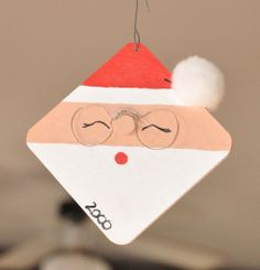 A wood square and some paint makes for a cute Santa face.  Add a pom pom and some wire glasses.  Family ornament 2000.