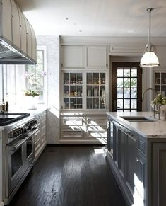 Taupe and grey kitchen by Tracery Interiors. Love the range hood, the contrast color island, the hand-scraped hardwood floors, the wall of floor-to-ceiling tile, and the door to the backyard. Understated and beautiful.