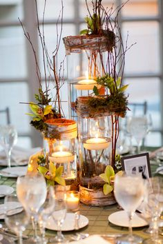 A little different twist on rustic centerpiece...bark and grape vine (?) wrapped around both top and bottom of cylinder vases, with floating candles inside.