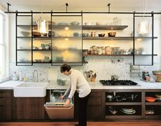 Instead of a solid, dark wall of cabinetry, a triptych of steel-framed cabinets with sliding textured-glass panels reveals objects on open walnut shelves while screening clutter.