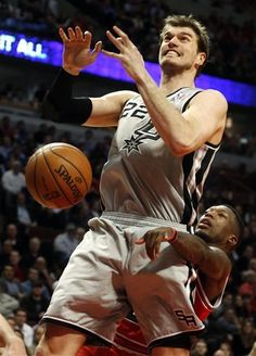 San Antonio Spurs center Tiago Splitter (22) is fouled from behind by Chicago Bulls guard Nate Robinson during the second half of an NBA basketball game, Monday, Feb. 11, 2013, in Chicago. The Spurs won 103-89. (AP Photo/Charles Rex Arbogast)