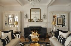 We are seeing double in this gorgeous cream and black sitting area with two sofas, mirrored armoires and black arm chairs. Bold gold accessories add a glam touch.