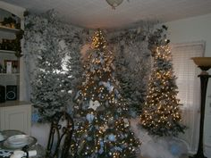 Bought cheap fake trees at thrift stores. Sprayed them with canned snow. Also, bought artif.. flowers and tree balls..then spray painted them the color I needed. After the paint dried,  I used spray glue.. and glittered the flowers and balls.