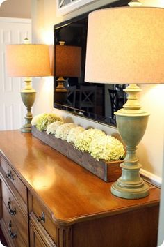 Long box of dried or faux hydrangeas under flat screen.