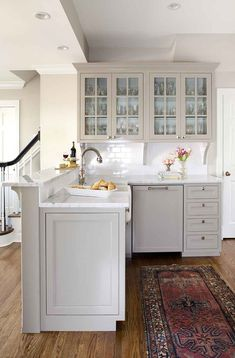 white kitchen wood floors rug cabinets glass paned
