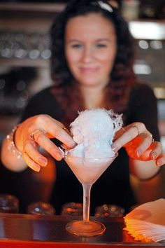 Urban Grill Signature Drink - Cotton Candy Martini - Take a chilled martini glass place an over-sized tuft of blue cotton candy inside. Add Pinnacle Cotton Candy Vodka, Kinky Liqueur and a secret fruit juice mixture (cranberry and sour mix) to a shaker with ice and vigorously shake.  Pour over cotton candy and enjoy!