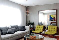No amplo estar, o painel de madeira cumaru sobe do chão à parede. A tubulação exposta dá contraste imediato. O cinza ganha pitadas de energia com tons de vermelho em estampas das almofadas e nas geometrias do tapete da Carbono Design