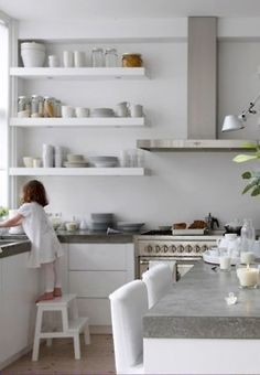 white kitchen cabinets with concrete counters & white floating shelves