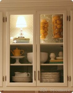 DIY:  How to convert wood cabinet doors into glass cabinet doors.  Very easy DIY. Love the lamp in the cabinet.
