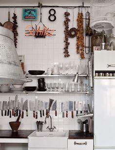 Una cocina en blanco llena de arte y objetos.  Zona fregadero