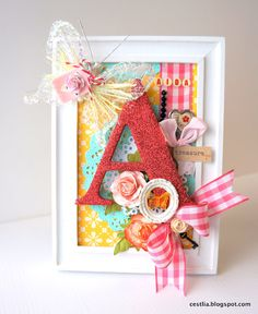 Frame for Aida. Monogram misted with Maya Mist Cherry Metallic Mist and glittered with Maya Road red glitter.