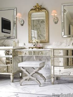 "Designer Carrie Hayden took the homeowners' bedroom dressers and connected them with a mirrored vanity table for a glamorous bathroom update. ""It's more Old World than Old Hollywood,"" she says. ""The mirrors on the vanity are antiqued, so it's a softer look."""