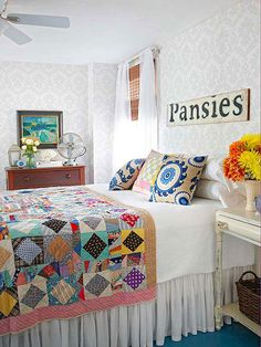Mix Old and New - A farm sign above the bed and a patchwork quilt help to give the bedroom a vintage vibe while graphic, modern pillows and light gray damask wallpaper leave the room feeling fresh and up-to-date.