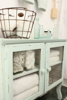this is a pretty/clean look i like it -A patinated wire basket, an assortment of old-fashioned glass bottles, and shelves full of crisp white towels give this painted cabinet a cottage-chic update.