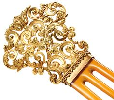 """Gold Hair Comb  Date: Circa 1900.     Solid gold of 14k has been formed into ornate and complex foliate forms and scroll motifs in an open work pattern. Completing the piece is a trio of honey colored natural horn prongs each formed into a tapered shape with a slight convex curve. Please note the Greek influence on the """"lintel"""" at the bottom of the gold top with its scalloped design.     Measurements: 4-3/4 inches (12.3 cm) in total length; gold top is 1-3/4 inches (4.5 cm) in length by 1-3/4..."""