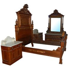 Beautiful four-piece antique walnut Victorian bedset attr: to Thomas Brooks. This set includes one highback bed, a marble top dresser with beveled mirror and two nightstands.