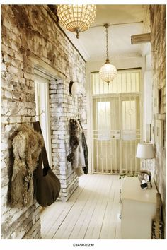 Exposed brick foyer with wood floors painted white.