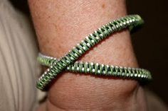 Zipper and Wire Bracelet.  Super easy - zipper and telephone wire (it's colored).  Now to find telephone wire!