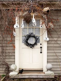 Turn autumn gourds into hanging ghost to scare of potential pranksters.  (Photo credit: bhg.com)