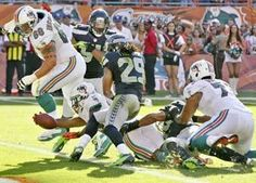 Dolphins running back Daniel Thomas stretches for 3-yard touchdown run, which came one play after Seattle was called for a costly roughing-the-passer penalty. The Dolphins beat the Seahawks, 24-21.