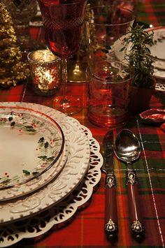 A table set w/Christmas dishes & a tartan tablecloth. So pretty!